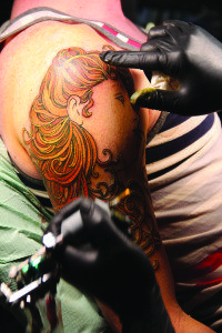 Adam Roach tattoos a man's arm at The Forge Tattoo. Photo by Molly Oleson.