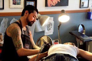 Marcelo Diaz Sepulveda tattoos a client at The Forge Tattoo. Photo by Molly Oleson.